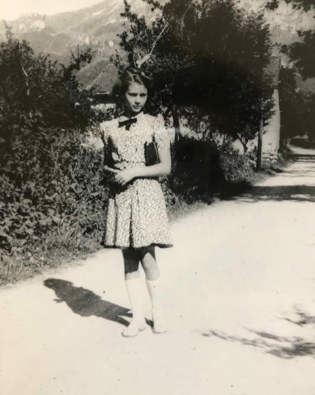 Mädchen posiert auf Gehweg.