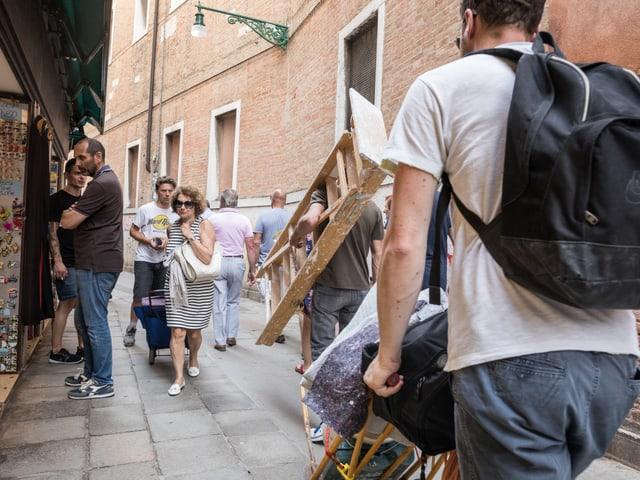 Ein mann mit einer Bauleiter geht an Touristen vorbei durch eine schmale Gasse.