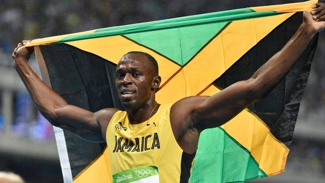 Usain Bolt cun la bandiera da la Jamaica suenter sia victoria sur 200 meters a Rio.