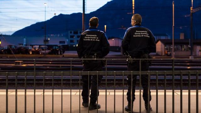 Zwei Grenzwächter bei Dämmerung auf einem Bahnperron, im Hintergrund ein Berg.