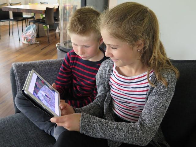 Zwei Kinder sitzen auf einem Sofa und blicken auf ein Tablet.