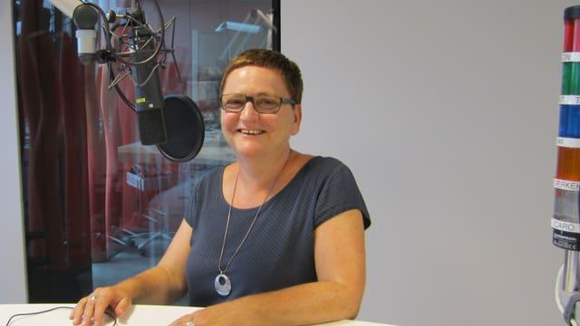 Eine Frau steht in einem Sendestudio hinter einem Mikrofon.