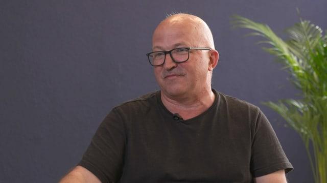 Ein Mann mit Glatze und T-Shirt in einer Interview-Situation.