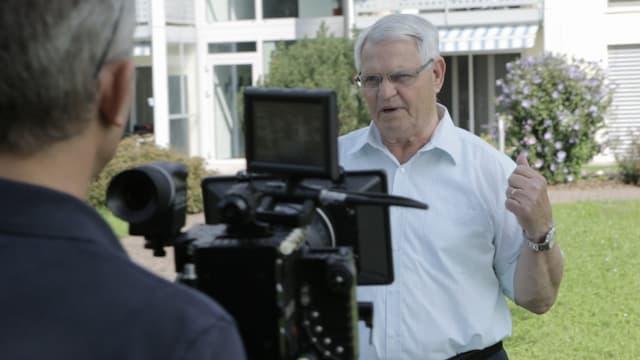 Kameramann filmt Anwohner vor Mehrfamilienhaus