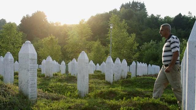 Weisse Grabsteine in mehreren Reihen, von rechts tritt ein Mann ins Bild.