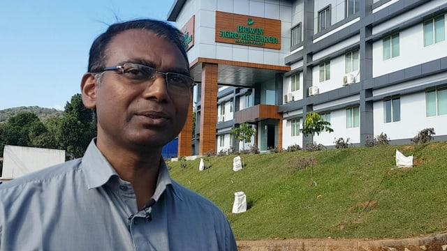 Ein Mann posiert vor einem Krankenhaus.