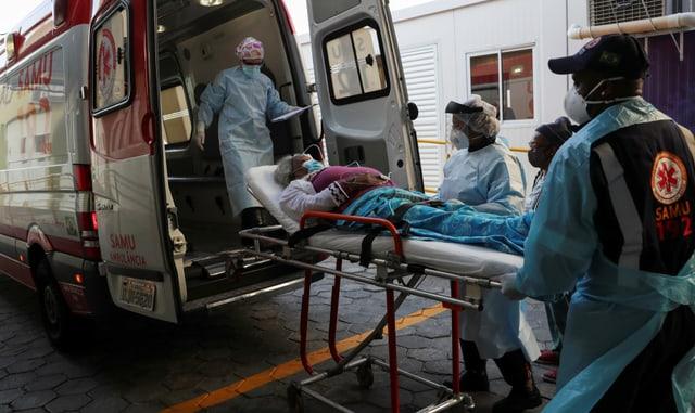 Eine Frau auf einer Trage wird von drei Pflegern in Schutzausrüstung in einen Krankenwagen verfrachtet.