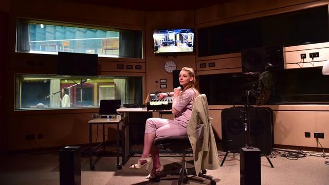 Frau in rosa Kleid in einem Tonstudio