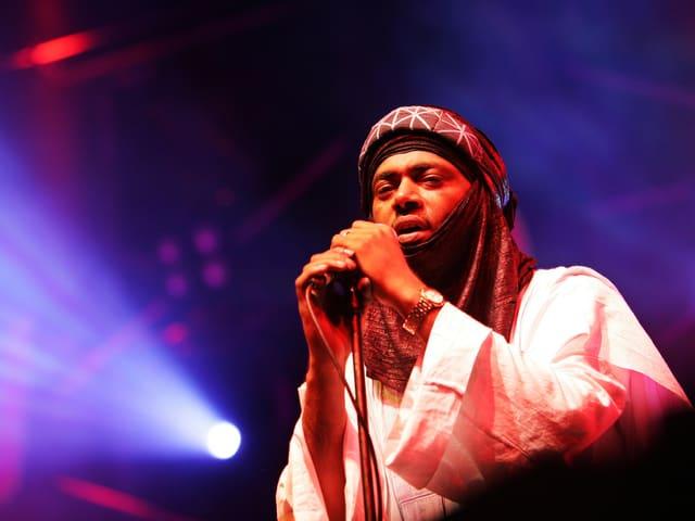 EIn arabischer Mann singt auf einer Bühne.