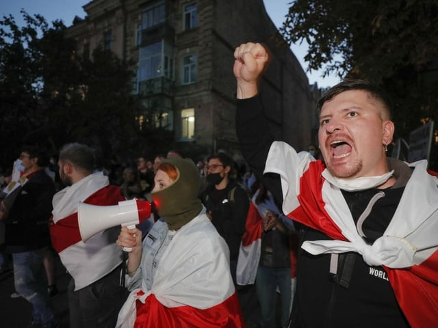 Protestierende schreien in ein Megafon, rufen Parolen und ballen die Faust in der Luft.