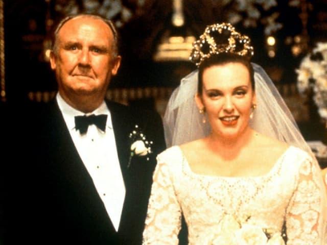 Toni Colette als im opulenten Brautkleid neben dem Brautvater.