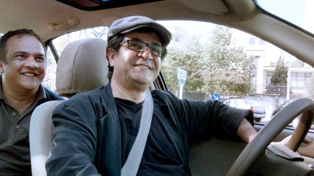 Blick in ein Auto mit einem Fahrer und einem Mann auf dem Rücksitz, der lächelnd nach vorne schaut.