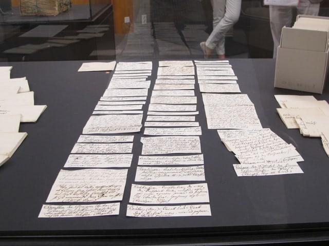 Zettel liegen geordnet auf einem Tisch.
