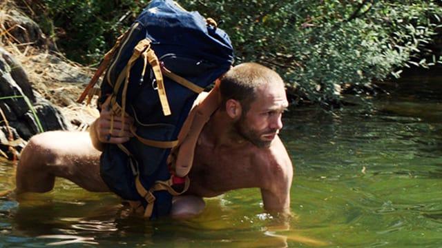 Mann in Unterwäsche lauert im Wasser und hält einen Rucksack über Wasser.