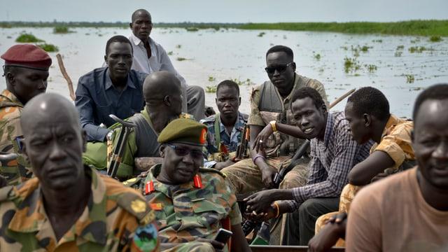Männer in Uniform und ohne in einer Gruppe an einem See.