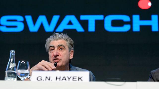 Nick Hayek spricht vor einem grossen Swatch Schriftzug in ein Mikrophon.