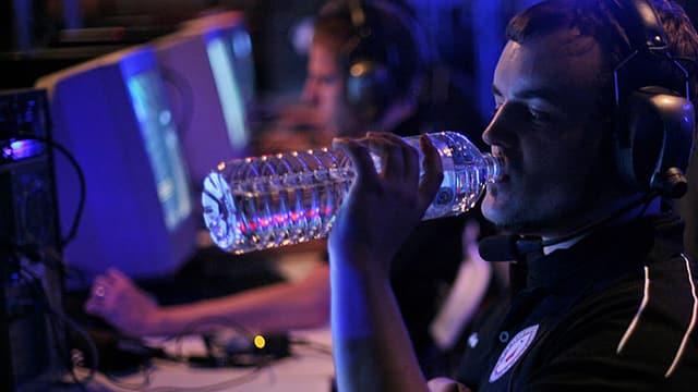 Ein junger Mann sitzt vor einem Computer und trinkt aus einer Wasserflasche.