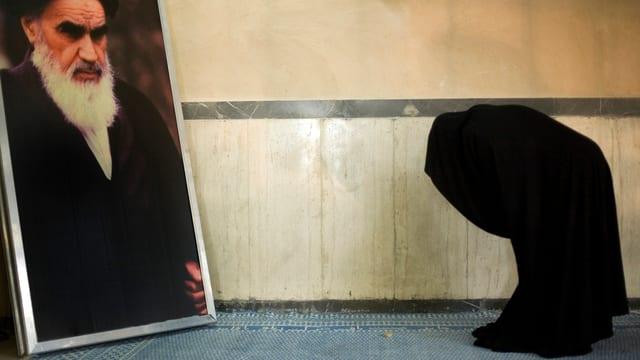 Frau mit Tschador vor Bild von Chomeini.