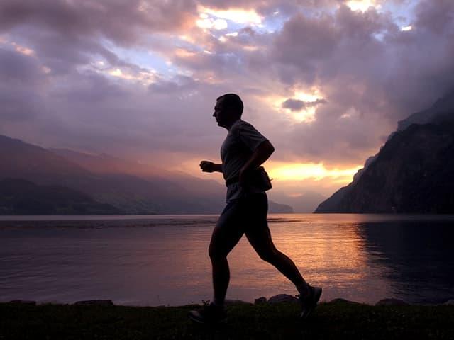 Dunkler Umriss einer joggenden Person, im Hintergrund violette Abendstimmung mit vielen Wolken, See und Berge.