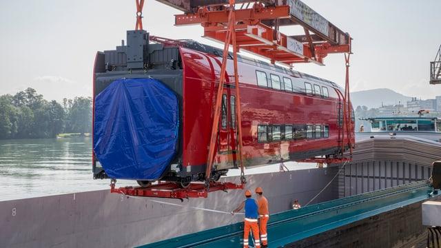 Ein Bahn-Waggon wird an einem Kran auf ein Schiff abgesetzt.