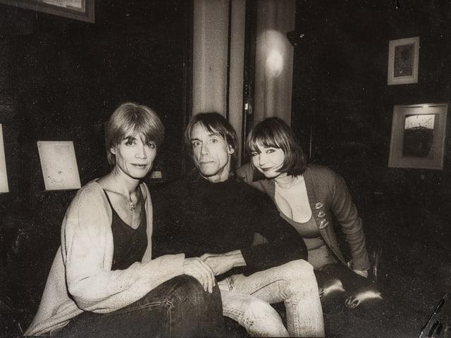 Schwarz-Weiss-Foto: Zwei Frauen und ein Mann sitzen nebeneinander und schauen in die Kamera.