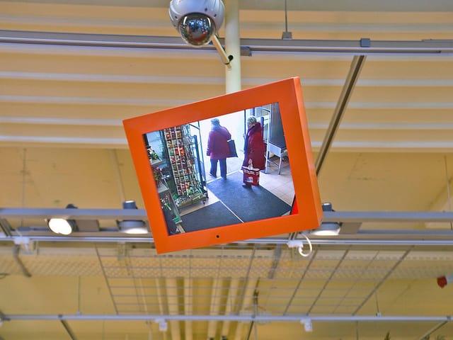 Eine Kamera an der Decke eines Supermarktes filmt die Kunden.