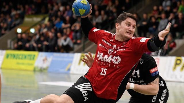 Ein Mann in einem roten Trikot wirft ein Handball.