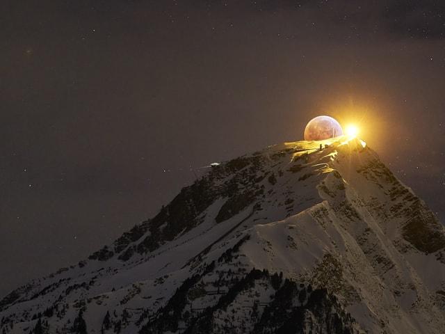 Der Mond geht hinter einem Berg auf.