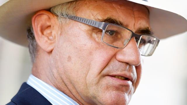Mann mit Brille und Hut schaut zur Seite