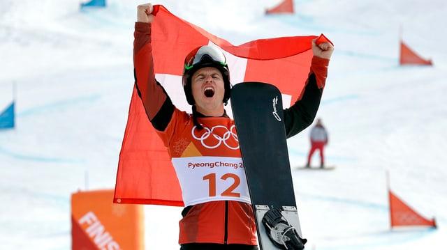 Mann hälft Schweizer Fahne in die Höhe und Snowboard in der Hand