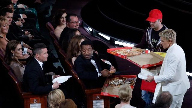 Ellen DeGeneres in den Publikumrängen eine Pizza verteilend.