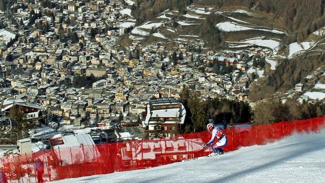 Ein Fahrer fährt über die Piste von Bormio, im Hintergrund die Ortschaft.