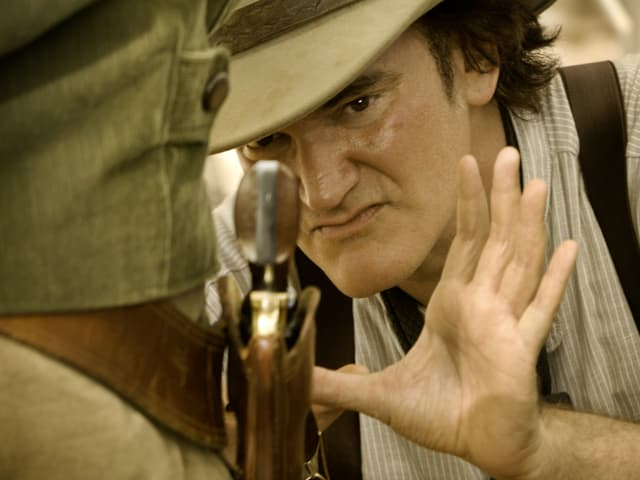 Quentin Tarantino zeigt mit der Hand auf eine Pistole, als solle jemand eine Nahaufnahme davon machen.