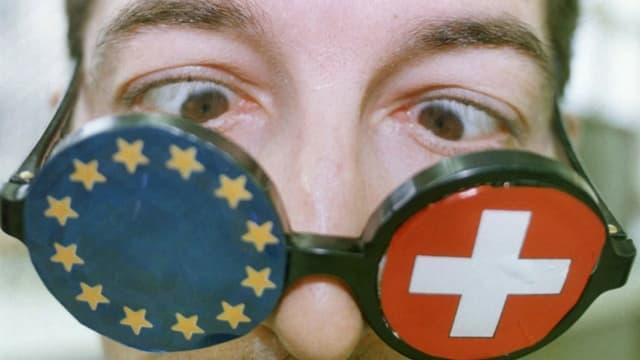 Ein Mann schielt durch eine Brille, auf deren einem Glas ein Schweizerkreuz, auf dem anderen eine EU-Flagge aufgeklebt sind.