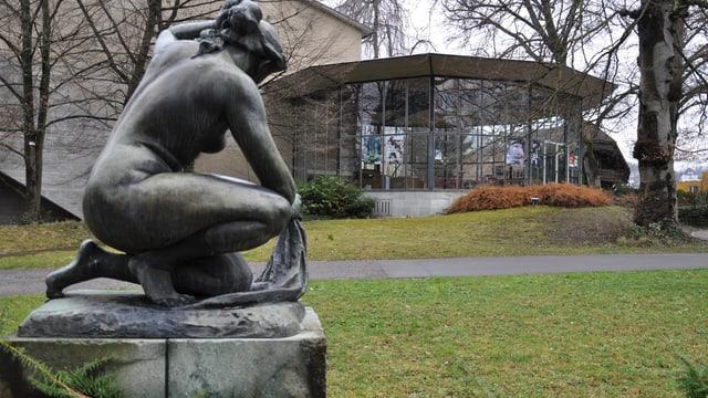 Das Glasfoyer aufgenommen an einem grauen Tag vom Kurpark aus. Im Vordergrund die Statue einer Frau.