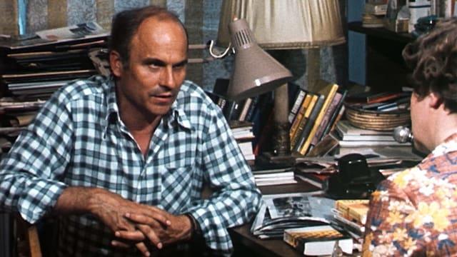 Ryszard Kapuściński sitzt an seinem Arbeitstisch und wird von einer Reporterin interviewt.