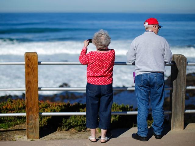 Rückansicht eines Rentnertpaares an einer Meeresküste, mit Blick zum Horizont.