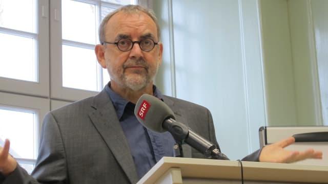 Ein Mann mit runder Brille und Kinnbart spricht in ein Mikrofon.