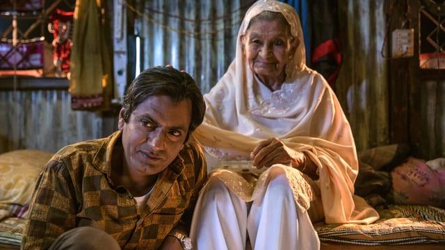 Ein Mann sitzt auf dem Boden, hinter ihm seine Grossmutter auf dem Bett. Sie trägt weiss.