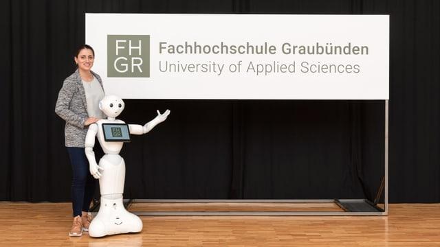 Ina studenta ha preschentà ensemen cun il roboter Pepper il Logo da la FH Grischun.
