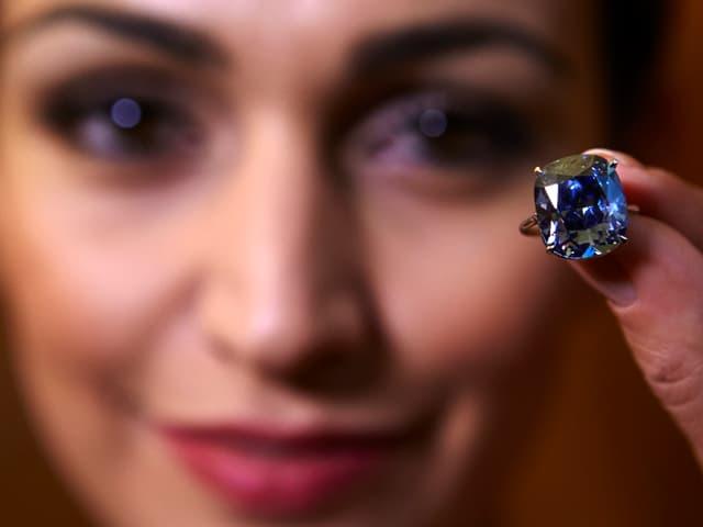 Frau hält Diamantring vor Gesicht