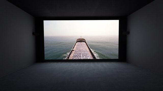 Vorführungsraum, auf der Leinwand ist ein Bild aus einem Film zu sehen: Ein Frachter auf dem Meer.