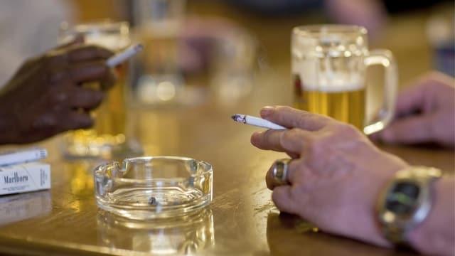 Menschen rauchen und trinken an einem Tisch.