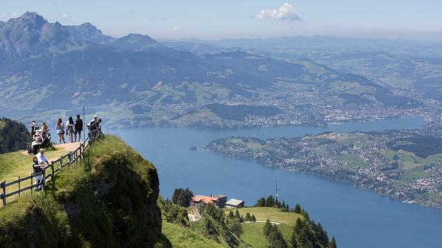 Menschen auf einem Berg über einem See.