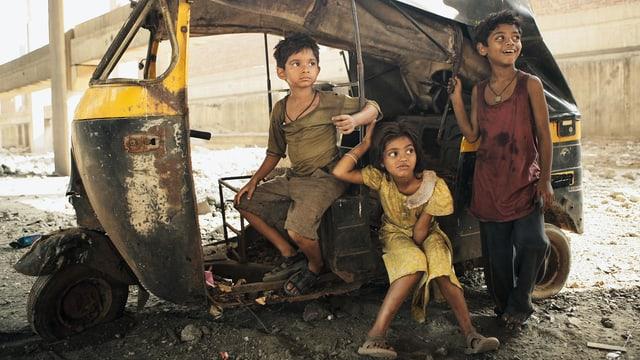 Drei indische Waisenkinder finden in einem ausgebrannten Wagen Unterschlupf.