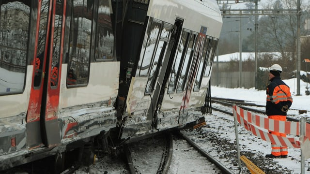 Gleisarbeiter vor aus den Schienen gesprungenem Zug.