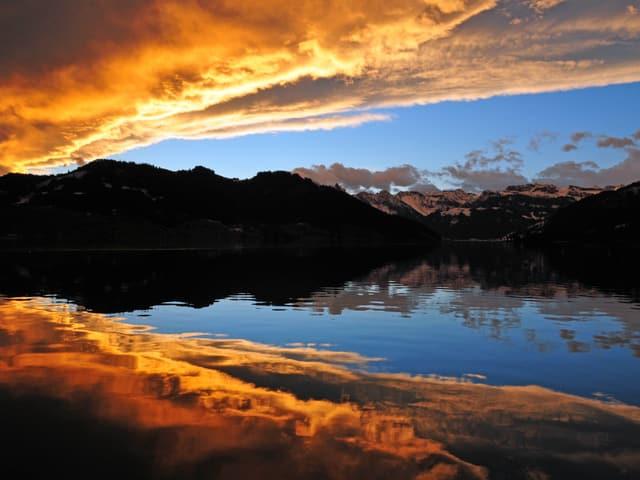 In einem See spiegeln sich die goldenen Wolken und das blaue Föhnfenster. Zwischen dem See und dem Himmel liegt eine dunkle Bergkette.