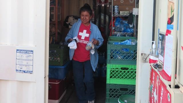 Vorratscontainer der Smaritans: Eine Frau mit rotem Shirt mit weissen Kreuz trägt etwas hinaus.