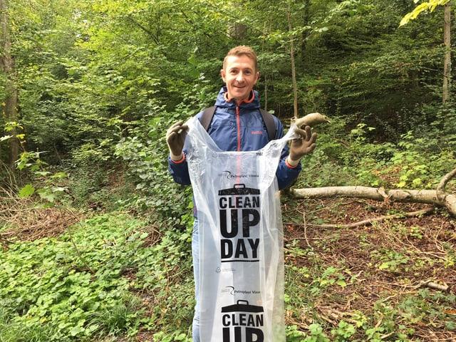 Mann mit Abfallsack im Wald.