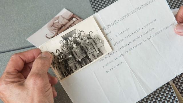 Hände, die ein altes Papier und ein schwarz-weiss Foto halten